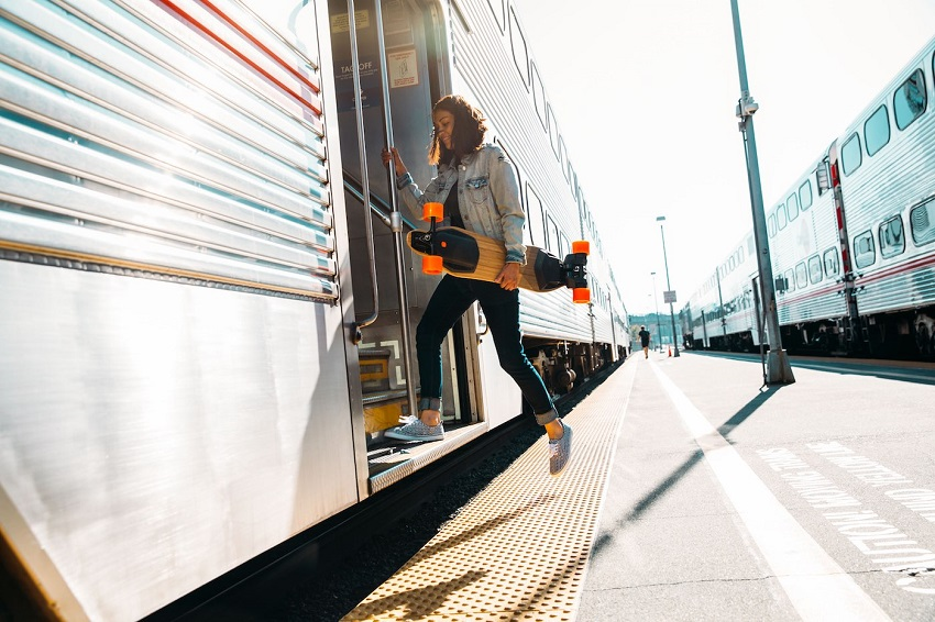 Girl getting on the train with boosted board