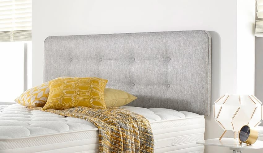 grey headboard for bedroom with white bedding and side table with a lamp