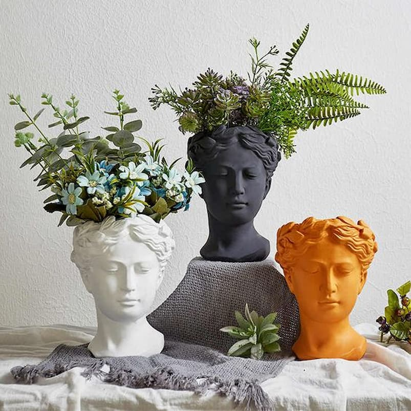 head sculpture with flowers growing inside